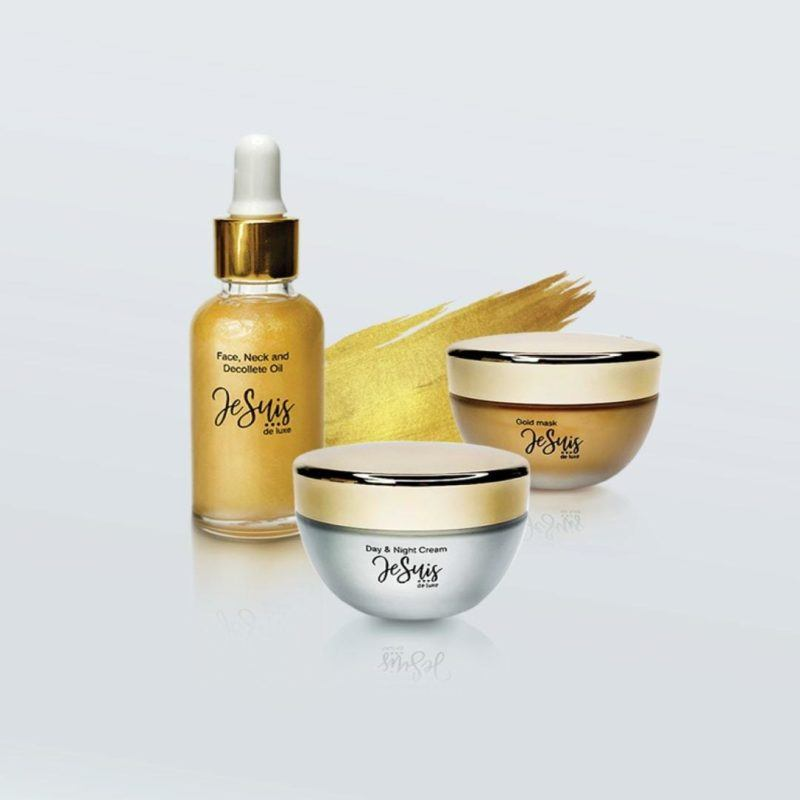 one bottle and two jars of gold cosmetics on white background