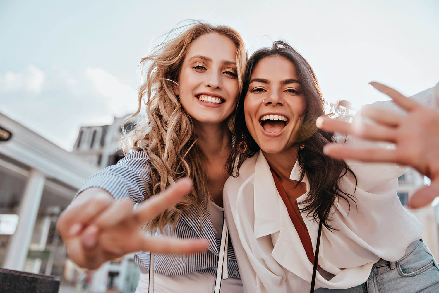 Two happy young women with theit hands pointing victory in camera