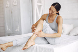 smiling woman sitting on bed applying body cream on her leg